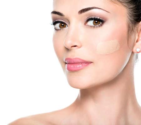 肌にファンデーションを持つ若い女性の美しい顔。  美容治療コンセプト