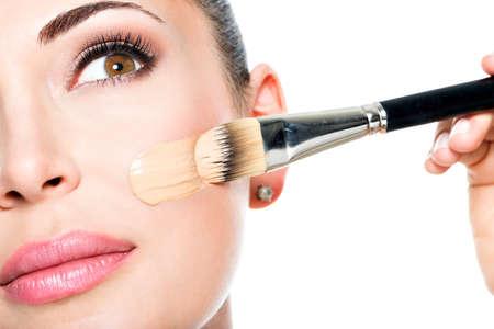 여자의 얼굴에 액체 톤의 기초를 적용하는 메이크업 아티스트
