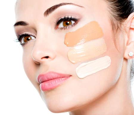 Mooi gezicht van jonge vrouw met cosmetische foundation op een huid. Schoonheidsbehandeling begrip