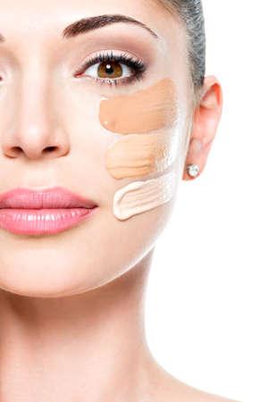 Bello fronte di giovane donna con fondazione cosmetica su una pelle. Concetto di trattamento di bellezza
