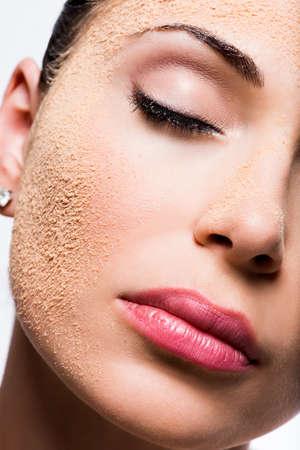 Visage d'une femme avec de la poudre cosmétique sur la peau - isolé sur blanc