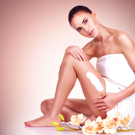 naked woman sitting: beautiful young woman with flowers using the cream LANG_EVOIMAGES