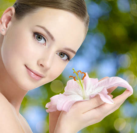 Healthy fresh face of beautiful young woman with lily flower in hands photo