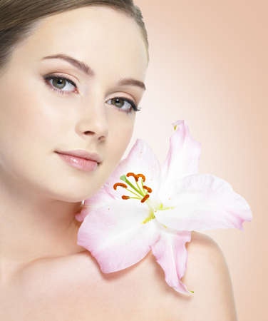 Portrait of beautiful healthy woman with flower at face photo