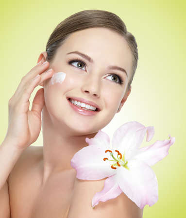 woman face cream: Beautiful young smiling woman with flower  applying cosmetic  cream on  face