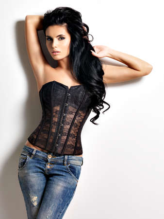 sexy style: Full portrait of the beautiful young sexy woman with long black  hair posing at studio dressed in the jeans and corset
