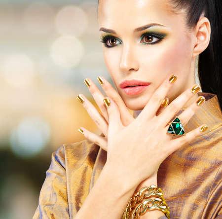 Glamour femme avec de beaux clous d'or et bague d'émeraude sur les mains