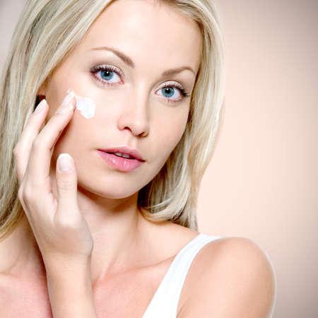 woman face cream: Beautiful woman applying cosmetic cream on face