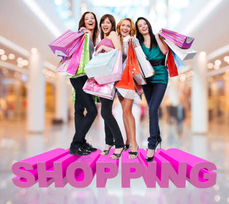 Happy women with shopping bags poses at store with three-dimensional text photo