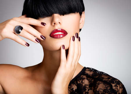 Closeup face of a woman with beautiful sexy red lips and dark nails - studio LANG_EVOIMAGES