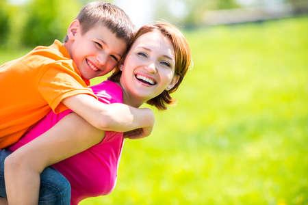 niños jugando en el parque: Madre e hijo felices en el prado de primavera retrato al aire libre