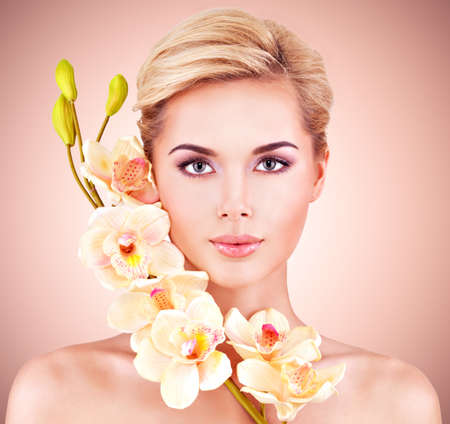 Young woman with health skin and flowers at face. Beauty treatment concept.