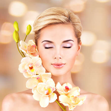 Closeup face of an young woman with health skin and flowers at face. Beauty treatment concept. LANG_EVOIMAGES