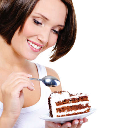 woman eating cake: Pretty young woman eats a sweet cake  isolated on white LANG_EVOIMAGES