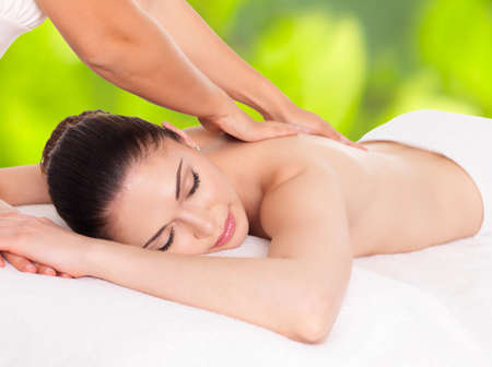 green back: Woman having massage of body in the spa salon over green nature background LANG_EVOIMAGES
