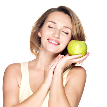 Young beautiful smiling woman touches the apple to face - isolated on white. Stock Photo