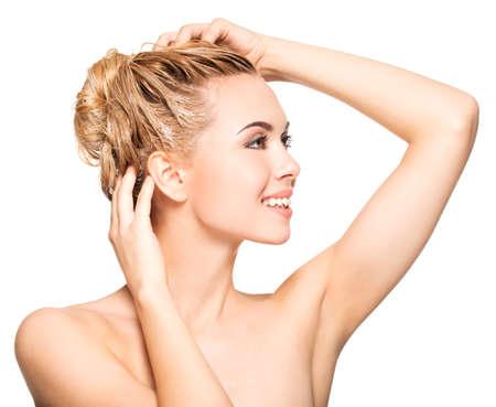 Portret van een lachende jonge vrouw was haar haren op een witte achtergrond Stockfoto