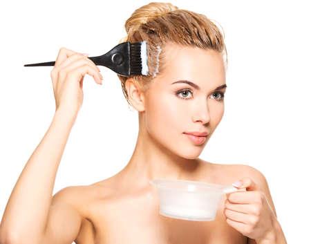 tinte cabello: Joven y bella mujer se tiñe el pelo. Aislado en blanco.