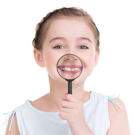 Close-up-Porträt von niedlichen kleinen Mädchen zeigt Zähne durch ein Vergrößerungsglas - isoliert auf weiß.