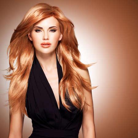 Mooie vrouw met lange rechte rood haar in een zwarte jurk. Mannequin poseren in studio. Stockfoto