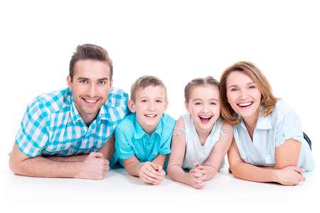 Kaukasische gelukkig lachende jonge gezin met twee kinderen liggend op de vloer