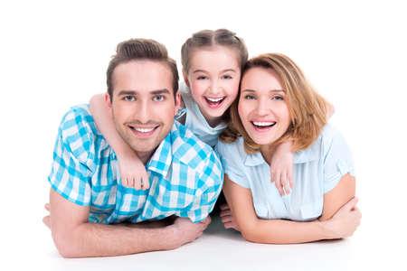 girl lying down: Cauc�sica feliz familia joven que sonr�e con la ni�a acostada en el piso