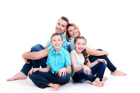 Europäischer glücklich lächelnde junge Familie mit zwei Kindern auf dem Boden sitzen