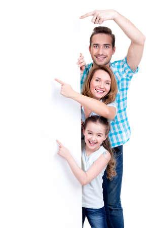 Retrato de una familia americana que apunta con el dedo a la bandera - aislados en un fondo blanco