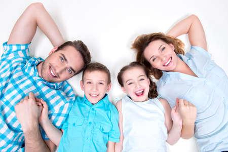 Hohe Winkel Portrait der kaukasischen glücklich lächelnde junge Familie mit zwei Kindern im Liegen auf weißen Boden und auf Kamera LANG_EVOIMAGES