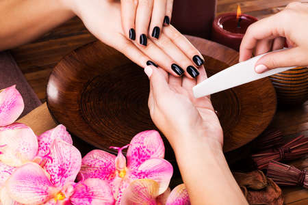 manicurist: Manicurist master  makes manicure on woman LANG_EVOIMAGES