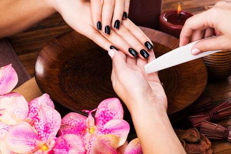 manicurist: Manicurist master  makes manicure on woman LANG_EVOIMAGES