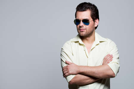 Portrait of handsome man in yellow shirt wearing sunglasses with crossed arms poses in the studio. Stock Photo
