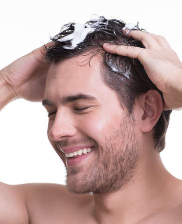 Young happy smiling man washing hair with closed eyes  - isolated on white. photo