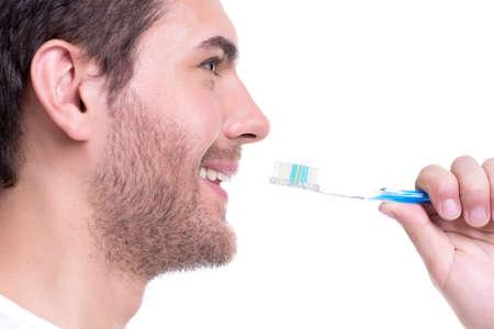 Profile close-up portrait of a happy young man with a toothbrush - isolated on white. photo