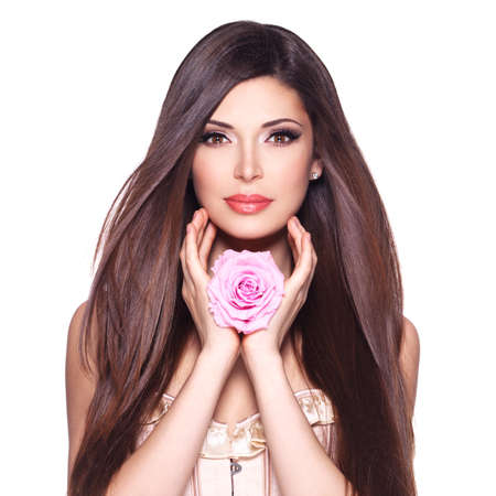Portrait of a beautiful white pretty woman with long straight hair and pink rose at face. LANG_EVOIMAGES