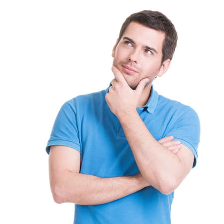 Portrait of the young thinking man looks up with hand near face -  isolated on white. Stock Photo