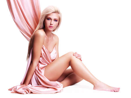 Sensual young woman with beautiful body in the pink silk sitting over white background. photo