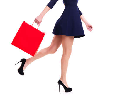 shopaholics: Woman in high heels with red shopping bag standing -  isolated on white.
