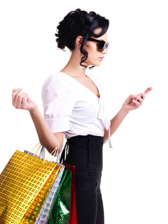 Portrait of a woman in glasses with shopping bags and mobile phone - isolated on white. photo