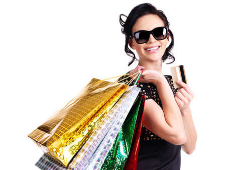 Happy woman in glasses with purchasing and credit card over white background. photo