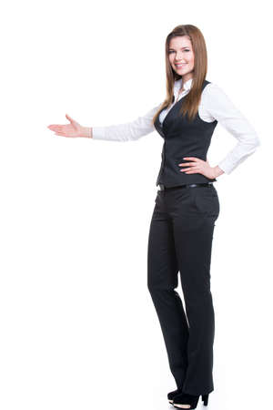 point: Young smiling happy woman in gray suit pointing at something by hand. isolated on white background.