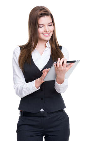 Beautiful young smiling business woman in a gray suit  using tablet on white background. photo
