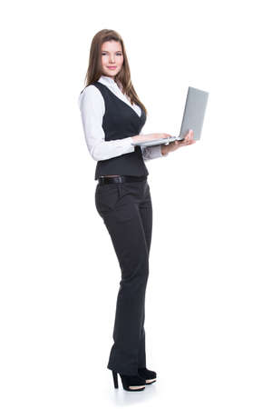 Portrait successful young business woman holding laptop in full length - isolated on white.   photo