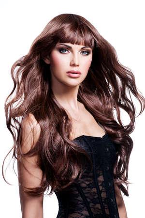 morena: Mujer hermosa joven con el pelo largo y castaño. Pretty modelo posa en el estudio.