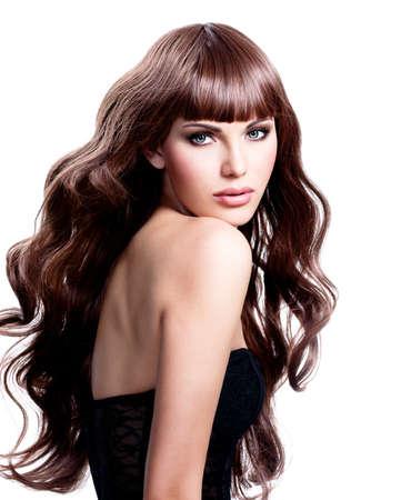 Belle jeune femme avec de longs cheveux bruns. Joli modèle pose au studio.
