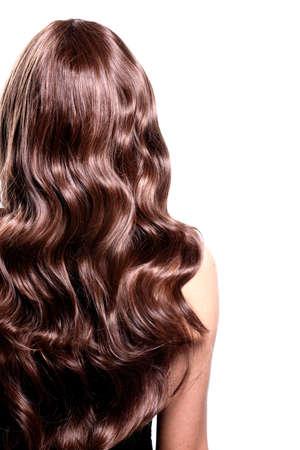 Vue arrière de femme brune avec de longs cheveux noirs bouclés posant au studio.