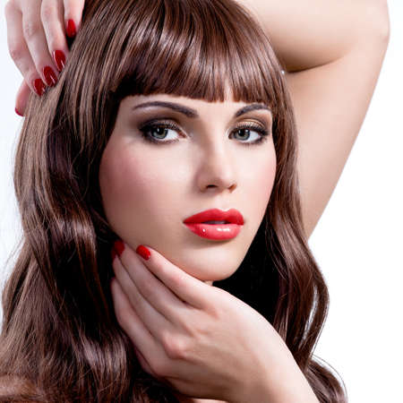 red hair woman: Photo of young woman with beauty long curly hair and bright makeup. Fashion model posing at studio.