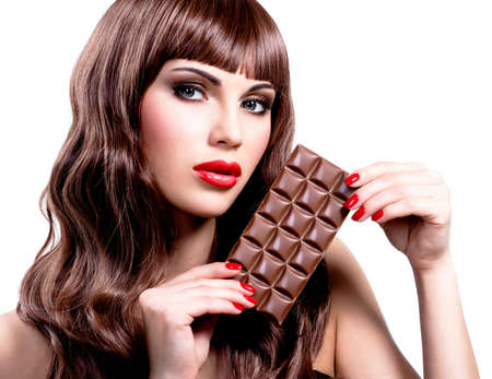 Portrait of beautiful sexy woman with bar of chocolate. Closeup face with bright makeup, isolated on white. photo