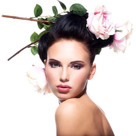 rosas blancas: Mujer hermosa joven con flores de color rosa en el pelo - aislado en blanco. Foto de archivo