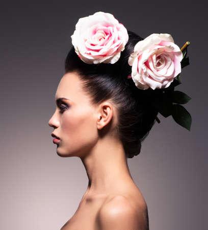 perfil de mujer rostro: Retrato de perfil de una hermosa mujer morena con el peinado creativo. Posando en el estudio. Foto de archivo